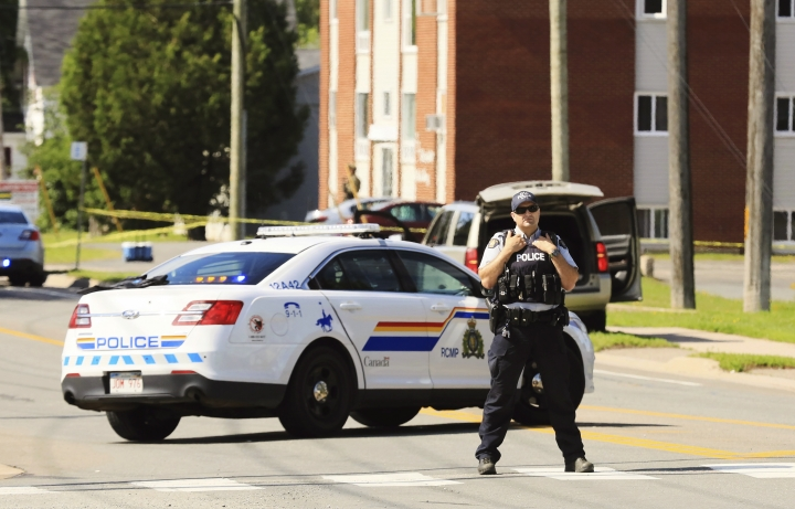 A police officer blocks the area of a shooting in Fredericton, New Brunswick, Canada on Friday, Aug. 10, 2018. Fredericton police say two officers were among four people who died in a shooting Friday in a residential area on the city's north side. One person was in custody, they said, and there was no further threat to the public. (Keith Minchin/The Canadian Press via AP)
