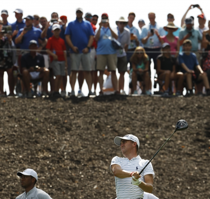 Spectators watch from above as Justin Thomas drives on the eighth hole as Tiger Woods watches at lower left, during the second round of the PGA Championship golf tournament at Bellerive Country Club, Friday, Aug. 10, 2018, in St. Louis. (AP Photo/Charlie Riedel)