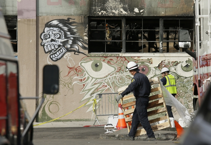 FILE - In this Wednesday, Dec. 7, 2016, file photo, a member of the Alameda County Sheriff's Department, left, carries away a pallet outside the site of a warehouse fire in Oakland, Calif. Two men who pleaded no contest to 36 charges of involuntary manslaughter will face the family members of those who died in the fire at an illegally converted Northern California warehouse. A two-day sentencing hearing for Derick Almena and Max Harris is scheduled to begin Thursday, Aug. 9, 2018, in Oakland. (AP Photo/Eric Risberg, File)