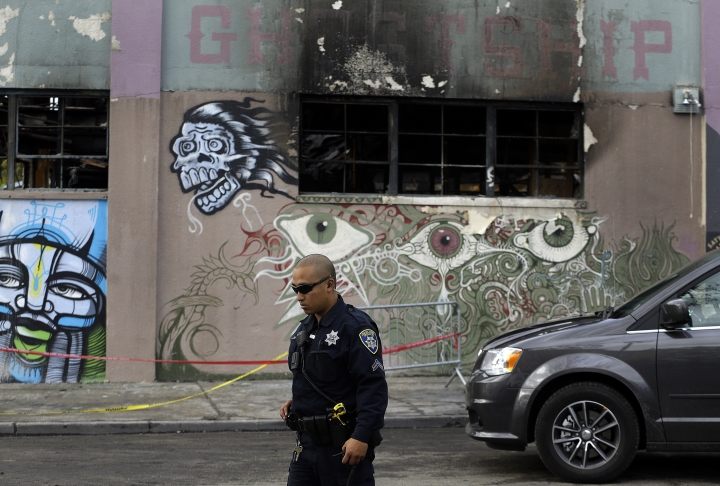 File - In this Dec. 9, 2016 file photo, an Oakland police officer guards the area in front of the art collective warehouse known as the Ghost Ship in the aftermath of a fire in Oakland, Calif. Two men who pleaded no contest to 36 charges of involuntary manslaughter will face the family members of those who died in a fire at an illegally converted Northern California warehouse. A two-day sentencing hearing for Derick Almena and Max Harris is scheduled to begin Thursday, Aug. 9, 2018, in Oakland. (AP Photo/Ben Margot, File)