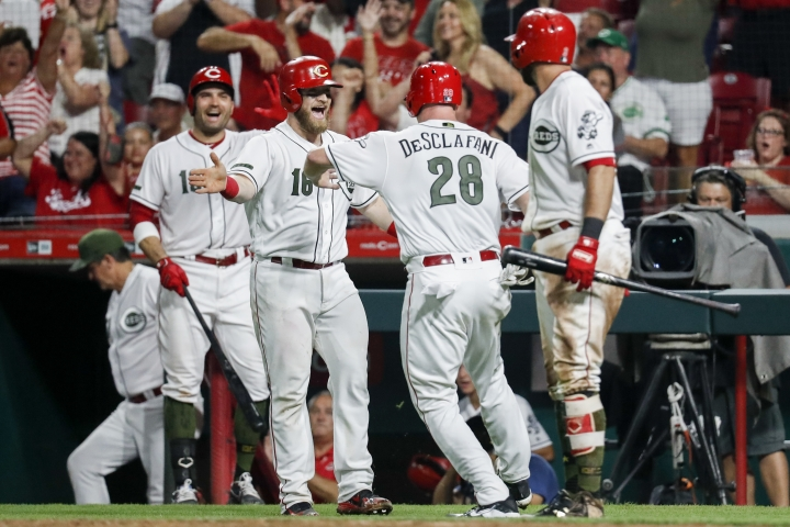 Cincinnati Reds' Anthony DeSclafani (28) celebrates with Tucker Barnhart (16) after they scored on a bunt single by Billy Hamilton off Arizona Diamondbacks starting pitcher Clay Buchholz and a throwing error by Buchholz during the seventh inning of a baseball game, Friday, Aug. 10, 2018, in Cincinnati. (AP Photo/John Minchillo)