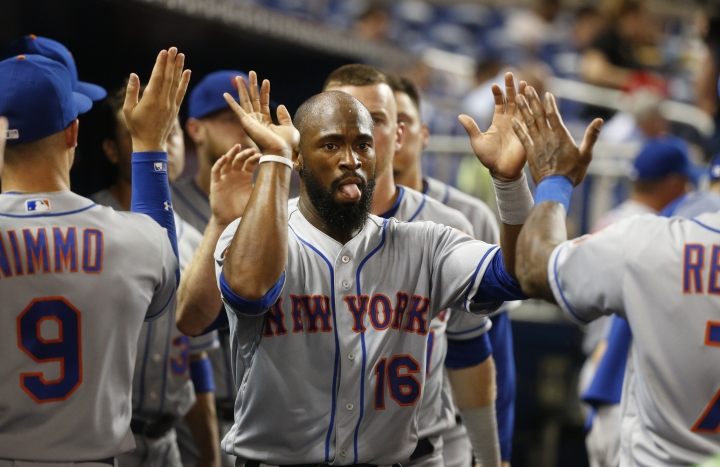 New York Mets' Austin Jackson (16) is congratulated by teammates after he and Todd Frazier scored on a single by Amed Rosario during the sixth inning of a baseball game against the Miami Marlins, Friday, Aug. 10, 2018, in Miami. (AP Photo/Wilfredo Lee)