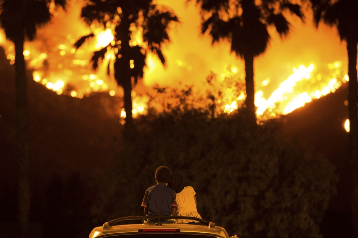 King Bass, 6, left, sits and watches the Holy Fire burn from on top of his parents' car as his sister Princess, 5, rests her head on his shoulder Thursday night, Aug. 9, 2018 in Lake Elsinore, Calif. More than a thousand firefighters battled to keep a raging Southern California forest fire from reaching foothill neighborhoods Friday before the expected return of blustery winds that drove the flames to new ferocity a day earlier. (AP Photo/Patrick Record)