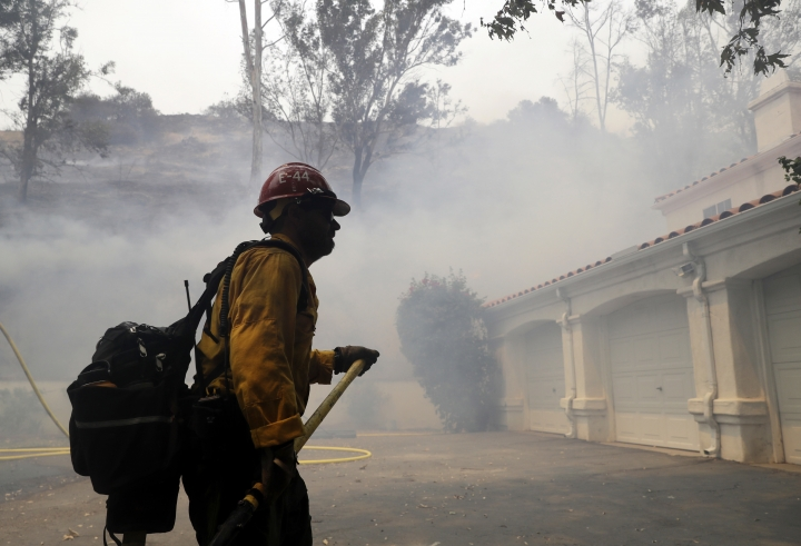 A firefighter walks in front of a home as smoke from an advancing wildfire fills the air Friday, Aug. 10, 2018, in Lake Elsinore, Calif. Firefighters are protecting foothill neighborhoods in the city of Lake Elsinore near where the blaze flared up amid unpredictable winds a day earlier. (AP Photo/Marcio Jose Sanchez)