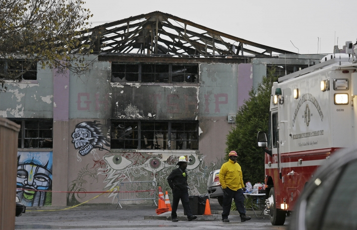 FILE - In this Dec. 7, 2016 file photo, Oakland fire officials walk past the remains of the Ghost Ship warehouse damaged from a deadly fire in Oakland, Calif. Two men who pleaded no contest to 36 charges of involuntary manslaughter will face the family members of those who died in a fire at an illegally converted Northern California warehouse. A two-day sentencing hearing for Derick Almena and Max Harris is scheduled to begin Thursday, Aug. 9, 2018, in Oakland. (AP Photo/Eric Risberg, File)