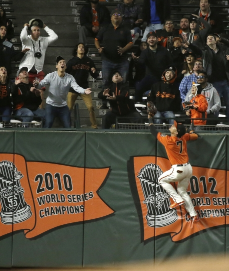 San Francisco Giants left fielder Gorkys Hernandez leaps up on the outfield wall and watches a home run hit by the Pittsburgh Pirates' Adeiny Hechavarria in the ninth inning of a baseball game Friday, Aug. 10, 2018, in San Francisco. San Francisco won the game 13-10. (AP Photo/Eric Risberg)