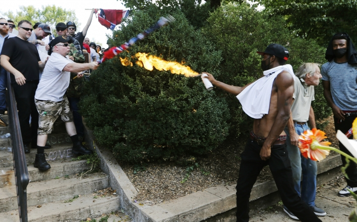 "FILE - In this Aug. 12, 2017, file photo, a counter demonstrator uses a lighted spray can against a white nationalist demonstrator at the entrance to Lee Park in Charlottesville, Va. There has been no reset, no moment of national healing. One year after blaming ""both sides"" for violent clashes between white supremacists and counterprotesters, President Donald Trump stills flirts with racially tinged rhetoric _ and feels little blowback from Republican leaders or GOP voters when he does. Black leaders and Democrats argue Trump's tone and actions on race have gotten even worse in the months since the clashes in Charlottesville, Virginia. (AP Photo/Steve Helber, File)"