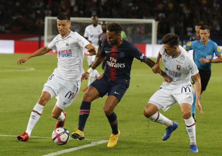 PSG's Neymar, center, challenge for the ball with Caen's Stef Peeters, left, during their League One soccer match between Paris Saint-Germain and Caen at Parc des Princes stadium in Paris, Sunday, Aug. 12, 2018. (AP Photo/Michel Euler)