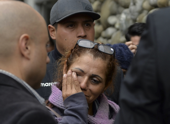 A woman cries as she arrives to find out news of soccer fans killed in a bus crash outside the morgue in Cuenca, Ecuador, Monday, Aug. 13, 2018. At least 12 fans of Ecuadorean football team Barcelona were killed and 30 injured when the bus they were traveling in after a match against Deportivo Cuenca overturned on Sunday. (AP Photo/Javier Ramirez)