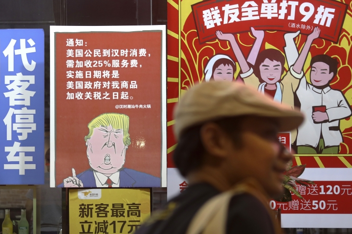 In this Monday, Aug. 13, 2018, photo, a man walks by a poster depicting a mural of U.S. President Donald Trump stating that all American costumers will be charged 25 percent more than others starting from the day president Trump started the trade war against China, on display outside a restaurant in Guangzhou in south China's Guangdong province. The recent trade war between the world's two biggest economies has forced many multinational companies to reschedule purchases and rethink where they buy materials and parts to try to dodge or blunt the effects of tit-for-tat tariffs between Washington and Beijing. (Color China Photo via AP)