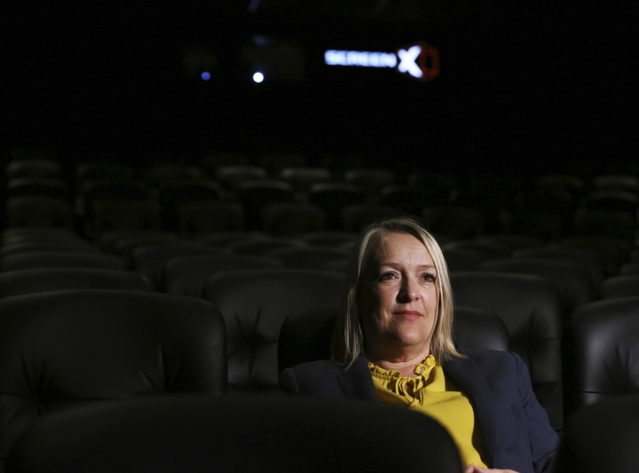 In this photo taken on Thursday, Aug. 9, 2018, Kelly Drew, an operations director at Cineworld, sits in the front row at Cineworld during a demonstration of ScreenX, a technology that projects films onto three screens, in London. Sit at the back of the movie theater, and it's possible to see the appeal of ScreenX, the latest attempt to drag film lovers off the sofa and away from Netflix. Instead of one screen, there are three, creating a 270-degree view meant to add to the immersive experience you can't get from the home TV. (AP Photo/Robert Stevens)