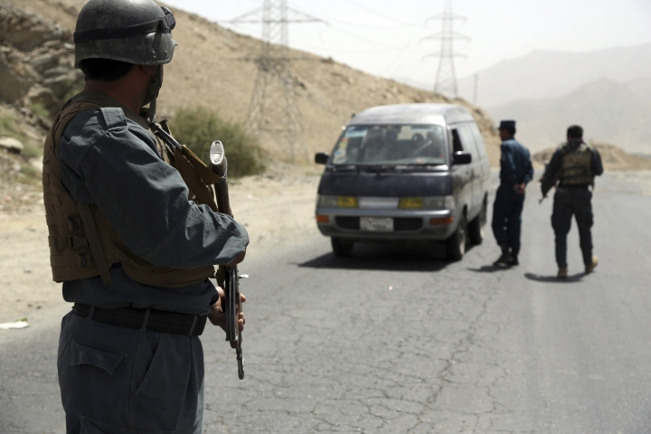 Afghan police officers search a vehicle at a checkpoint on the Ghazni highway, in Maidan Shar, west of Kabul, Afghanistan, Monday, Aug. 13, 2018. Afghan Defense Minister Gen. Tareq Shah Bahrami said Monday that about 100 policemen and soldiers as well as 20 civilians have been killed in past four days of battle in the eastern capital of Ghazni. (AP Photo/Rahmat Gul)