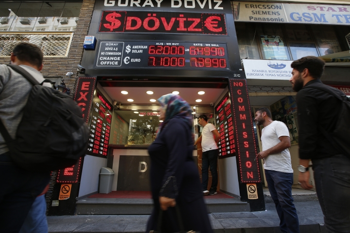 People walk past a currency exchange shop in Istanbul, Tuesday, Aug. 14, 2018.The Turkish lira has nosedived in value in the past week over concerns about Turkey's President Recep Tayyip Erdogan's economic policies and after the United States slapped sanctions on Turkey angered by the continued detention of an American pastor. (AP Photo/Burhan Ozbilici)