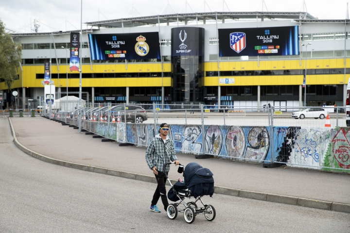 A man pushes baby in a stroller in front of the Lillekula Stadium, a day ahead of UEFA Super Cup final soccer match between Real Madrid and Atletico Madrid in Tallinn, Estonia, Tuesday, Aug. 14, 2018. (AP Photo/Pavel Golovkin)