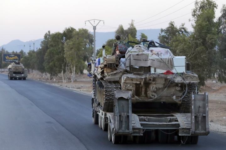 Syrian military move along a road near the village of Almajdiyeh, Syria, Tuesday, Aug. 14, 2018. The Russian military said Tuesday that its forces in Syria will help U.N. peacekeepers fully restore patrols along the frontier with the Israeli-occupied Golan Heights, reflecting Moscow's deepening role in mediating between the decades-old foes. (AP Photo/Sergei Grits)
