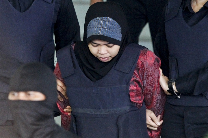 FILE - In this March 22, 2018, file photo, Indonesian Siti Aisyah is escorted by police as she leaves after a court hearing at Shah Alam High Court in Shah Alam, Malaysia. Siti Aisyah and Vietnam's Doan Thi Huong, two Southeast Asian women on trial in Malaysia for the brazen assassination of the North Korean leader's half-brother could be acquitted Thursday, Aug. 16, 2018, or called to enter their defense in a case that has gripped the world. The two are accused of smearing VX nerve agent on Kim Jong Nam's face in a crowded airport terminal in Kuala Lumpur on Feb. 13, 2017. The women have said they thought they were taking part in a prank for a hidden-camera show.(AP Photo/Sadiq Asyraf, File)