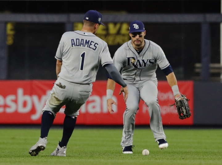 Tampa Bay Rays shortstop Willy Adames (1) and a teammate watch a ball hit by New York Yankees' Aaron Hicks for an RBI single land between them during the first inning of a baseball game Tuesday, Aug. 14, 2018, in New York. (AP Photo/Frank Franklin II)