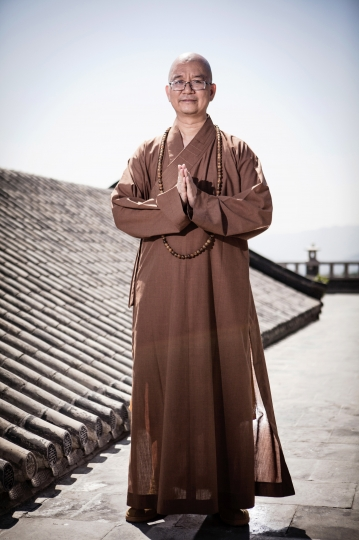 In this July 3, 2015, photo, Shi Xuecheng of the Beijing Longquan Temple poses for a photo outside one of the temple buildings in Beijing, China. One of China's most high-profile Buddhist monks has resigned from a top national post following reports of sexual misconduct, a religious association said Wednesday, Aug. 15, 2018. (Chinatopix via AP)