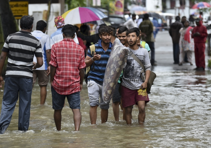 Laborers hailing from northern states wade through flood waters as they shift to higher grounds following heavy rains in Thiruvananthapuram, Kerala state, India, Wednesday, Aug. 15, 2018. Torrential monsoon rains have disrupted air and train services in the southern Indian state of Kerala where flooding, landslides, house and road bridge collapses have killed more than 40 people in the past week, officials said Wednesday. (AP Photo)