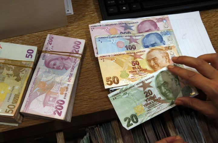 A worker at a currency exchange shop worker lays out Turkish lira banknotes depicting modern Turkey's founder Mustafa Kemal Ataturk, in Istanbul, Wednesday, Aug. 15, 2018. The Turkish lira has nosedived in value in the past week, but some Turks are reacting with defiance to their plunging currency and an escalating trade and political dispute with the United States, in an indication that they are ready to endure economic pain and risk further deterioration in a key yet troubled alliance dating from the Cold War. (AP Photo/Lefteris Pitarakis)