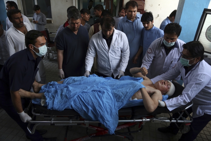An injured man is put into an ambulance following a deadly suicide bombing that targeted a training class in a private building in the Shiite neighbourhood of Dasht-i Barcha, in western Kabul, Afghanistan, Wednesday, Aug. 15, 2018. The public Health Ministry said the casualty toll has risen to at least 48 dead and dozens wounded. (AP Photo/Rahmat Gul)