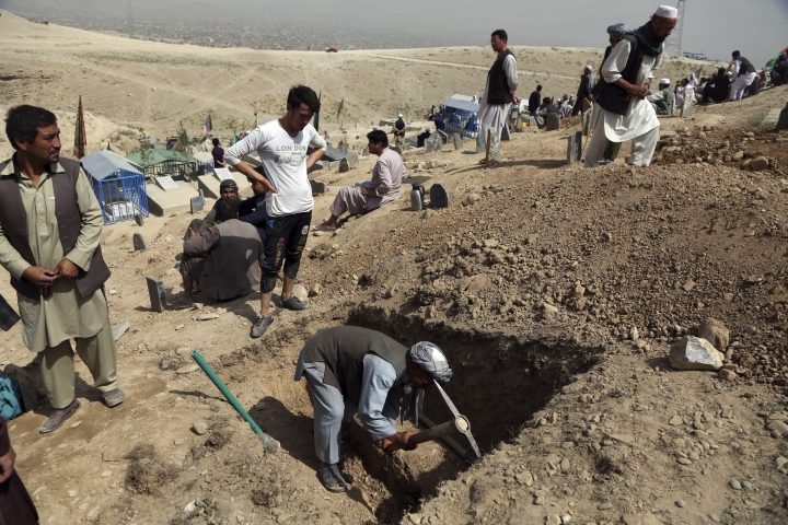 Afghan men prepare the graves for the victims of Wednesday's deadly suicide bombing that targeted a training class in a private building in the Shiite neighborhood of Dasht-i Barcha, in western Kabul, Afghanistan, Thursday, Aug. 16, 2018. The Afghan authorities have revised the death toll from the previous day's horrific suicide bombing in a Shiite area of Kabul to 34 killed. (AP Photo/Rahmat Gul)