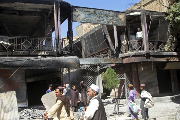 Afghan men stand in front of burned out shops following a Taliban attack in Ghazni, Afghanistan, Wednesday, Aug. 15, 2018. A Taliban assault on two adjacent checkpoints in northern Afghanistan killed at least 30 soldiers and police, officials said Wednesday. Life gradually returned to normal in parts of the eastern city of Ghazni after a massive insurgent attack last week, with sporadic gunbattles still underway in some neighborhoods. (AP Photo/Rahmatullah Nikzad)