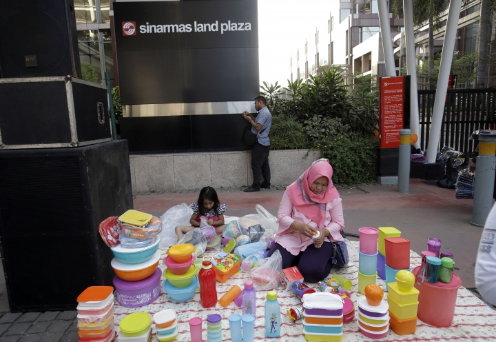 In this Aug. 5, 2018, photo, a mother sells food and beverage containers in front of building that houses the headquarters of Sinarmas Group, one of Indonesia's largest palm oil company, in Jakarta, Indonesia. The main global group for certifying sustainable wood has suspended plans to give its influential endorsement to Indonesian paper giant Sinarmas after revelations it cut down tropical forests and used an opaque corporate structure to hide its activities. (AP Photo/Tatan Syuflana)