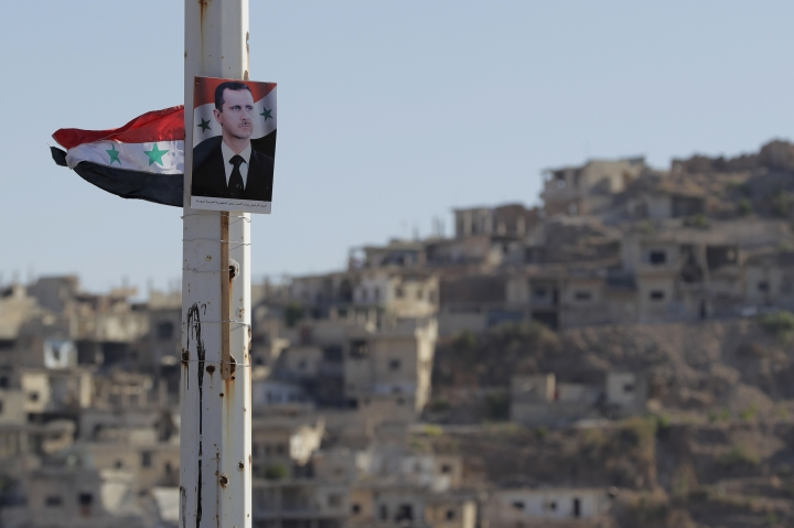A portrait of Syrian President Bashar Assad is fastened on the pillar in the town of Rastan, Syria, Wednesday, Aug. 15, 2018. The Russian Defense Ministry said Wednesday it is coordinating efforts to help Syrian refugees return home and rebuild the country's infrastructure destroyed by the civil war. (AP Photo/Sergei Grits)
