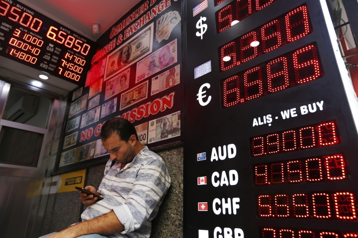 A man sits in a currency exchange shop in Istanbul, Thursday, Aug. 16, 2018.Turkey's finance chief tried to reassure thousands of international investors on a conference call Thursday, in which he pledged to fix the economic troubles that have seen the country spiral into a currency crisis.The national currency recovered somewhat from record lows hit earlier this week. (AP Photo/Lefteris Pitarakis)