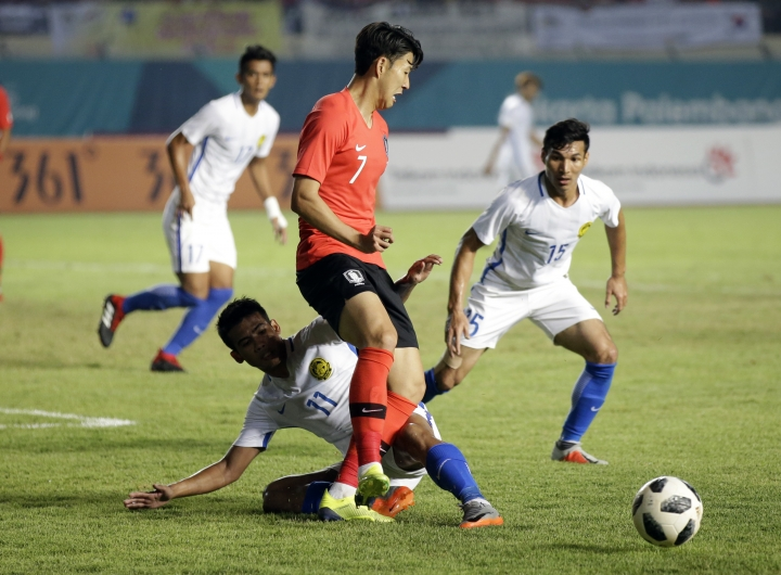 South Korea's Son Heung-min, center, battles for the ball with Malaysia's Muhammad Safari Rasid, bottom, and Mohd Rizal Ghazali during their men's soccer match at the 18th Asian Games at Si Jalak Harupat Stadium in Bandung, Indonesia, Friday, Aug. 17, 2018. (AP Photo/ Achmad Ibrahim )