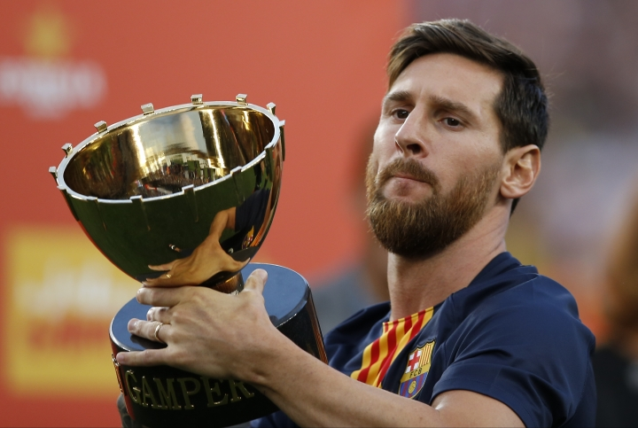 FC Barcelona's Lionel Messi holds up the Joan Gamper trophy after a friendly soccer match between FC Barcelona and Boca Juniors at the Camp Nou stadium in Barcelona, Spain, Wednesday, Aug. 15, 2018. (AP Photo/Manu Fernandez)
