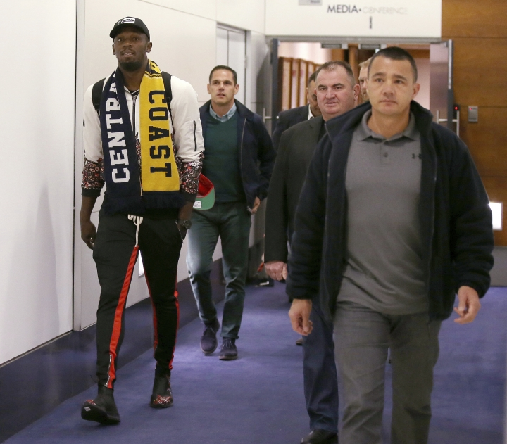 Jamaica's Usain Bolt, left, arrives in Sydney, Saturday, Aug. 18, 2018. Olympic gold medalist, Bolt is hoping to impress the coaching staff enough to earn a contract with the Central Coast Mariners for the 2018-19 season in Australia's top-flight soccer competition. (AP Photo/Rick Rycroft)