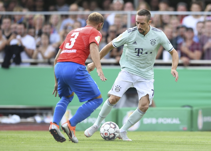 Bayern's Franck Ribery, right, and Drochtersen's Meikel Klee challenge for the ball during the German Soccer Cup, DFB-Pokal, match between fourth league club SV Drochtersen/Assel and Bayern Munich in Drochtersen, northern Germany, Saturday, Aug. 18, 2018. (Carmen Jaspersen/dpa via AP)