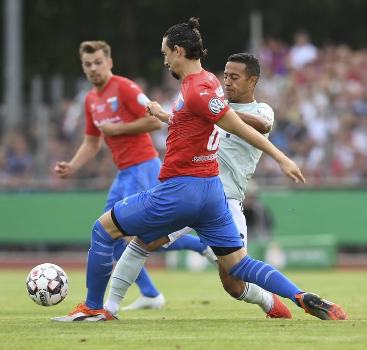 Bayern's Thiago, right, and Marcel Andrijanic of Drochtersen/Assel challenge for the ball during the German Soccer Cup, DFB-Pokal, match between fourth league club SV Drochtersen/Assel and Bayern Munich in Drochtersen, northern Germany, Saturday, Aug. 18, 2018. (Carmen Jaspersen/dpa via AP)