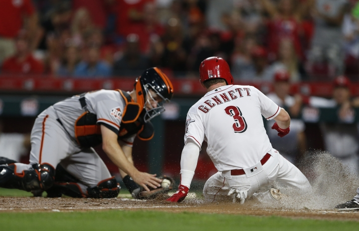 Cincinnati Reds' Scooter Gennett (3) scores on a sacrifice fly by Phillip Ervin as San Francisco Giants catcher Buster Posey, left, takes the throw during the fifth inning of a baseball game Saturday, Aug. 18, 2018, in Cincinnati. (AP Photo/Gary Landers)