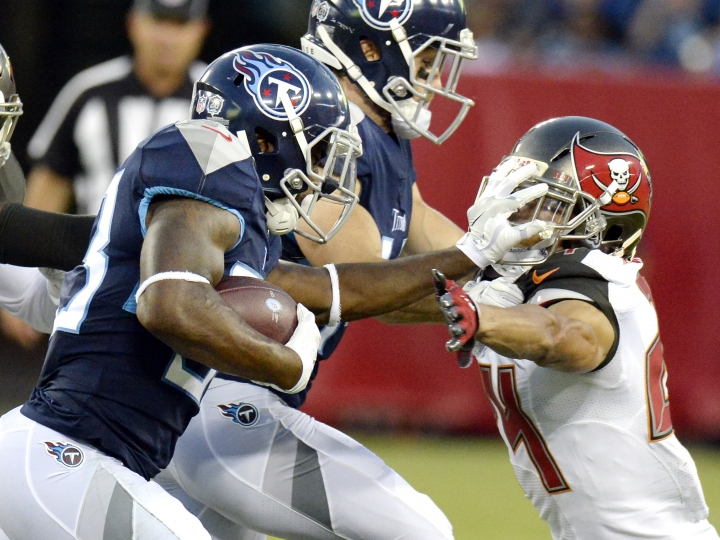 Tennessee Titans running back Dion Lewis, left, pushes Tampa Bay Buccaneers defensive back Brent Grimes (24) away in the first half of a preseason NFL football game Saturday, Aug. 18, 2018, in Nashville, Tenn. (AP Photo/Mark Zaleski))