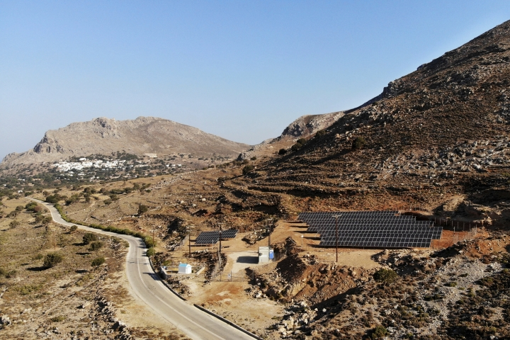 In this Thursday, Aug. 9, 2018, photo a road leads past a solar park on the Aegean island of Tilos, Greece. Tilos with its winter population of 400 and summer population of some 3000, will become the first island in the Mediterranean to run exclusively on wind and solar power when the blades of the 800 kilowatt wind turbine start turning. (AP Photo/ Iliana Mier)