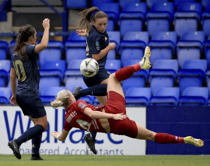 Liverpool Women's Rhiannon Roberts, down, and Manchester United Women's Kirsty Hanson, top, in action during a domestic cup game at Prenton Park in Liverpool, England, Sunday Aug. 19, 2018. In its first competitive game in 13 years, Man United's women's side beat Liverpool 1-0 in a domestic cup game that marked a new era on Sunday. (Clint Hughes/PA via AP)