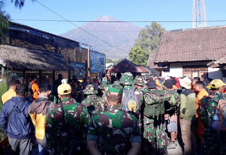 FILE - In this July 30, 2018, file photo, Indonesian soldiers and rescue team gather to prepare for evacuating tourists from Mount Rinjani, seen in the background, at Sembalun in East Lombok, Indonesia. A strong earthquake jolted the Indonesian island of Lombok on Sunday, Aug. 19, 2018, causing landslides on Mount Rinjani and damaging buildings, as it tries to recover from a temblor earlier this month that killed 460 people.(AP Photo/File)