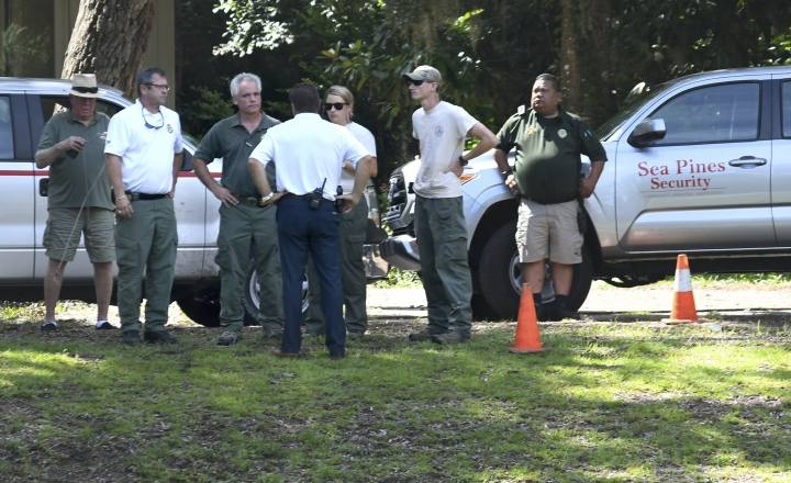 Law enforcement with Sea Pines Security, S.C. Department of Natural Resources and the Beaufort County Sheriff's Office stand near where authorities say Cassandra Cline was dragged into a lagoon by an alligator and killed while trying to save her dog on Monday, Aug. 20, 2018, on Hilton Head Island, S.C. Cline was walking the dog along a residential area of Sea Pines Resort when she was attacked, state and local officials said. (Drew Martin/The Island Packet via AP)