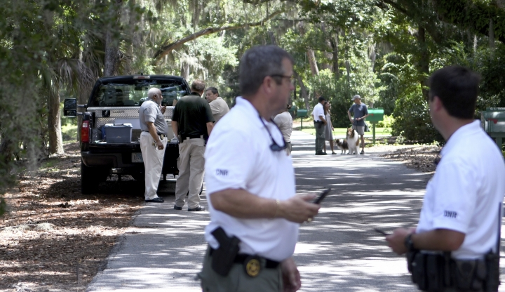 Beaufort County coroner Ed Allen, back left, talks with law enforcement with S.C. Department of Natural Resources as other officers stand near where authorities say Cassandra Cline was dragged into a lagoon by an alligator and killed while trying to save her dog Monday, Aug. 20, 2018, on Hilton Head Island, S.C. Cline was walking the dog along a residential area of Sea Pines Resort when she was attacked, state and local officials said. (Drew Martin/The Island Packet via AP)