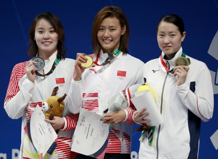 Women's 50m backstroke gold medalist China's Liu Xiang, centre, stands with silver medalist China's Fu Yuanhui, left, and bronze medalist Japan's Natsumi Sakai on the podium during the swimming competition at the 18th Asian Games in Jakarta, Indonesia, Tuesday, Aug. 21, 2018. (AP Photo/Bernat Armangue)