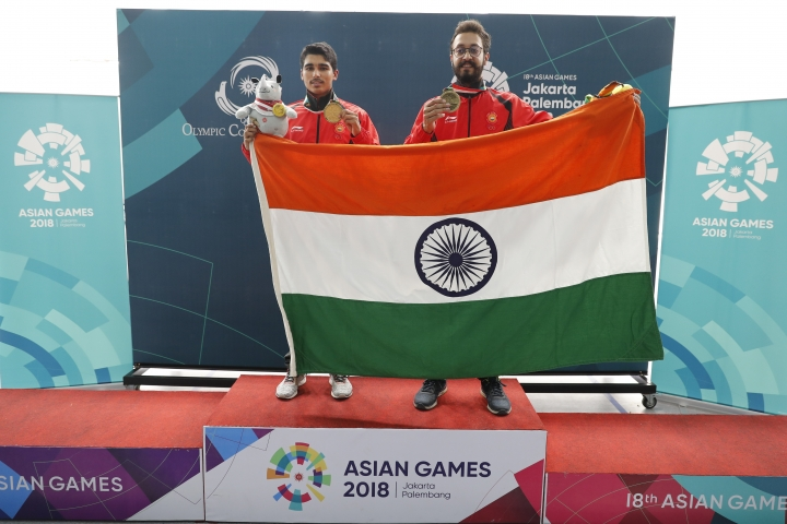 Bonze medalist India's Abhishek Verma, right, and gold medalist India's Saurabh Chaudhary, poses for photographer with India national flag after the 10m air pistol men's final shooting event during the 18th Asian Games in Palembang, Indonesia, Tuesday, Aug. 21, 2018. (AP Photo/Vincent Thian)