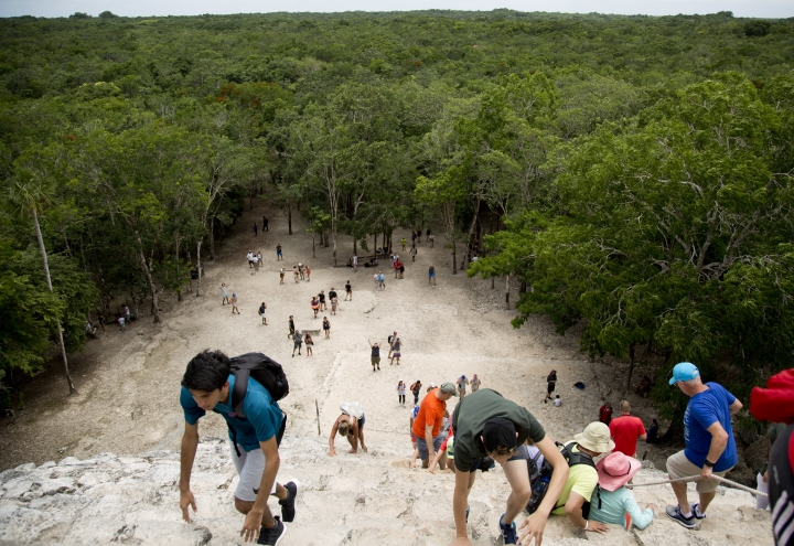 FILE- In this Aug. 1, 2018 photo, tourists climb a temple at the archeological site of Coba, in Mexico's Yucatan Peninsula. Whether you're planning a trip to a country across the globe or packing the car for a weekend road trip to a local campground, you can have a debt-free vacation with some careful planning. (AP Photo/Eduardo Verdugo, File)