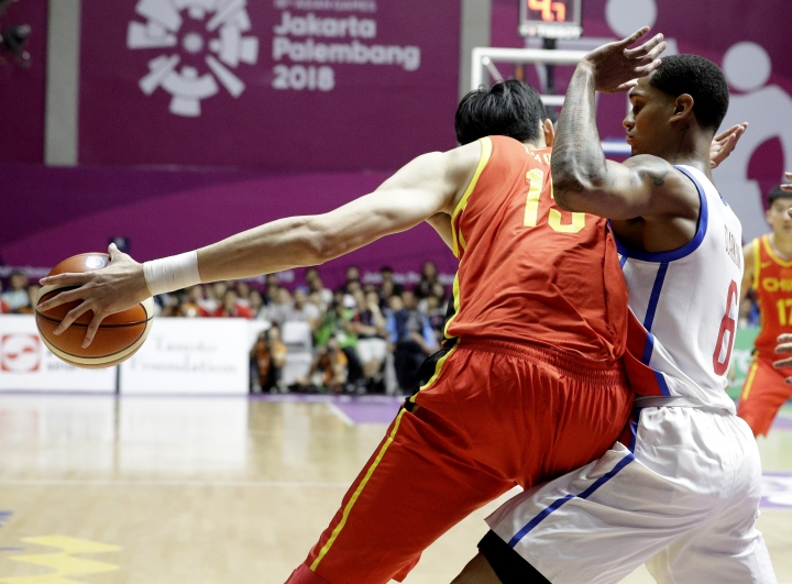 China'sQi Zhou, left, runs at Philippines' Jordan Clarkson during their men's basketball game at the 18th Asian Games in Jakarta, Indonesia on Tuesday, Aug. 21, 2018. (AP Photo/Aaron Favila)