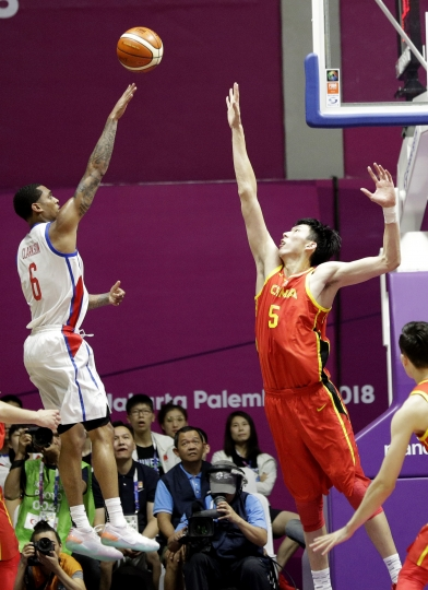 Philippines' Jordan Clarkson takes a shot at the basket as China's Shuo Fang attempts to block during their men's basketball game at the 18th Asian Games in Jakarta, Indonesia on Tuesday, Aug. 21, 2018. (AP Photo/Aaron Favila)