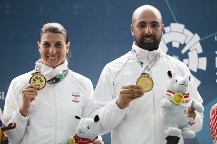 Gold medalist Lebanon's Ray Bassil, left, and her teammate Alain Moussa, shows their medals during awards ceremony for the trap mixed team Final shooting event during the 18th Asian Games in Palembang, Indonesia, Tuesday, Aug. 21, 2018. (AP Photo/Vincent Thian)