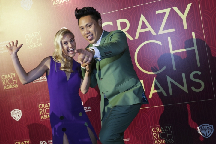 """Director John Chu and his wife Kristin Hodge pose for photographers as they arrive for the red carpet screening of the movie """"Crazy Rich Asians"""" on Tuesday, Aug. 21, 2018, in Singapore. (AP Photo/Don Wong)"""