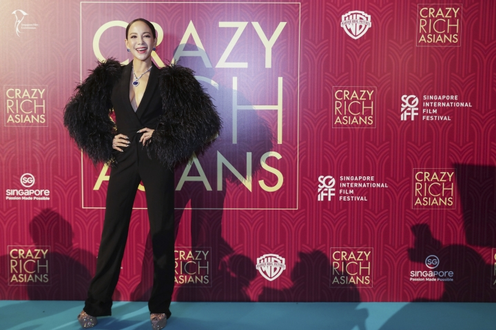 "Actress Fiona Xie poses for photographers as she arrives for the red carpet screening of the movie ""Crazy Rich Asians"" on Tuesday, Aug. 21, 2018, in Singapore. (AP Photo/Don Wong)"